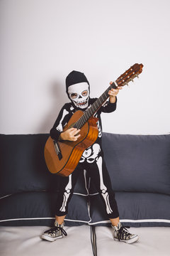Little boy in a skeleton costume playing a guitar
