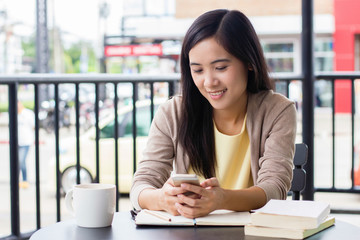 Asian woman using phone in the table inside coffee shop with blurry background of city