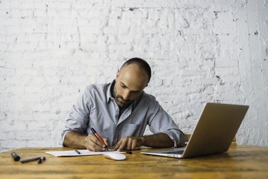 Senior designer working at laptop and sketches