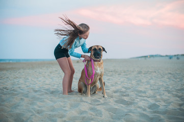 A tween girl comforts her large dog at the beach at sunset.