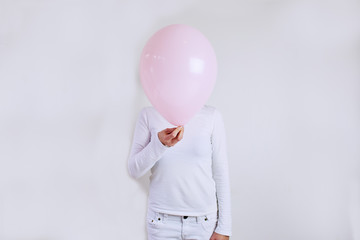 Young woman holding a pink balloon in front of her face