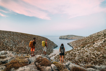 A group of hikers enjoying a sunset view over a scenic greek cove