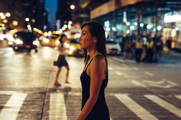 Asian woman crossing the road at night