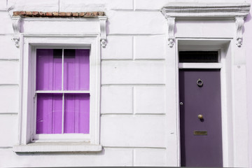 Facade of a Victorian residential building with bright violet window and door on a white wall