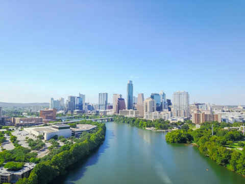 Aerial view green Austin state capital of Texas, USA with downtown skyscraper from Lady Bird Lake. People paddle kayak along Colorado River during sunny summer day. Travel and architecture background
