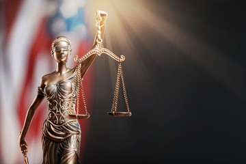 Statue of justice on flag background.