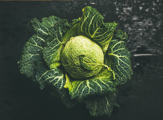 Raw fresh green cabbage over dark background, top view, selective focus, horizontal composition