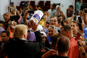 U.S. President Trump tosses rolls of paper towels to people at a hurricane relief distribution center at Calvary Chapel in San Juan