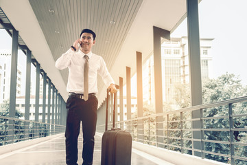 Handsome business asian man talking at mobile and holding suitcase at building walkway.