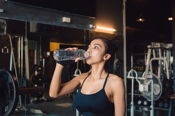 Young asian woman drinking water with refreshing during training at gym.