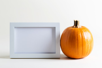 Blank white picture frame with a pumpkin on a white background