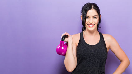 Happy young woman working out with a kettlebell Wall mural