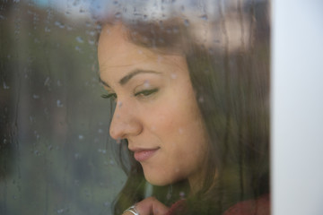 Beautiful woman is looking through the window on a rainy day.
