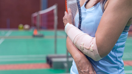 injured woman wearing sportswear  painful arm  and leg with gauze bandage, arm cast holding badminton racket standing on badminton court.