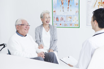 A young doctor is talking with an elderly couple in the examination room