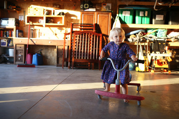 Little Girl Playing on Ride on Scooter in Garage