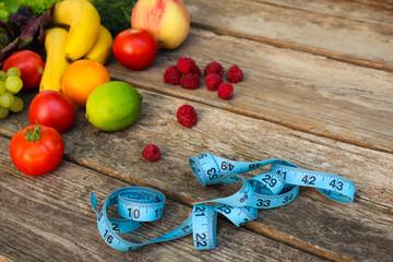 Fruits, vegetables, measure tape on wooden background.