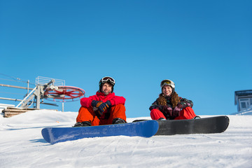 Guy and girl snowboarders are sitting on the snow at the top of the ski slope against the blue sky on a sunny day. Couple looking at camera and smiling