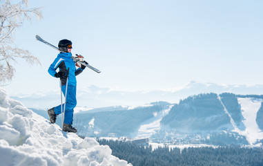 Full length shot of a female skier walking down the slope with her skis on the shoulder, copyspace winter ski resort and mountains on the background