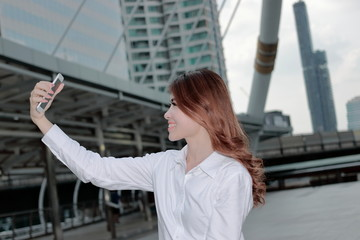 Side view of attractive young Asian woman taking a selfie photo at urban city  background.