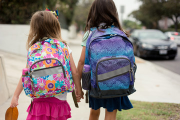 Two girls are walking to school holding hands on their first day wearing backpacks.