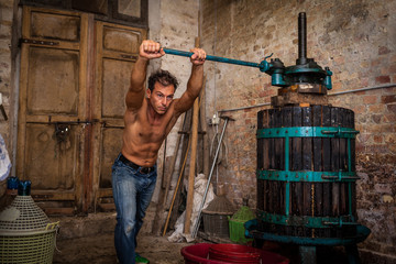 Shirtless winemaker farmer working on a traditional wine press
