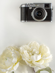 Black camera with flowers on the white table