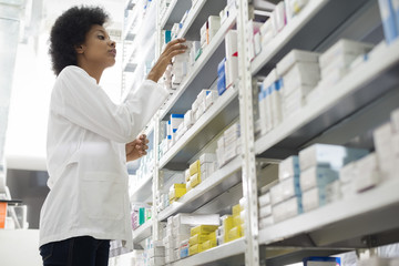 Female Chemist Arranging Stock In Shelves At Pharmacy
