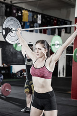 Woman Lifting Barbell While Standing In Fitness Studio