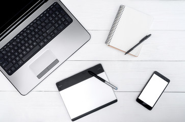 Top view on white wooden table with open laptop computer, blank cell phone, empty diary and graphic tablet, free space. Mobile phone with white screen, copy space