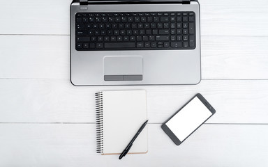 Top view on white wooden table with open blank laptop computer, cell phone, and empty diary with pen, free space. Mobile phone with white screen, copy space