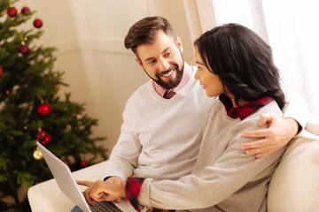 Lovable couple choosing Christmas presents online