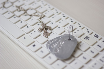 silver chain with a cross lying on a white keyboard