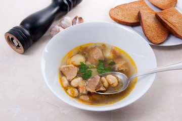Bean soup in white plate with metal spoon, several toast on white plate on a light stone background.