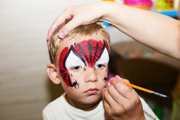 Master making aqua makeup on boys face
