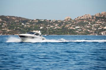 Small motor boat on sea, Sardinia island in background