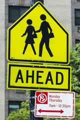 Warning sign of pedestrians crossing road ahead near school