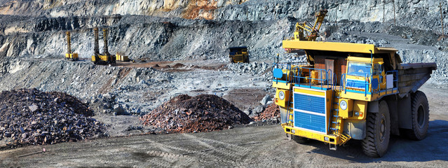 Heavy dump truck carrying the iron ore on the opencast mining