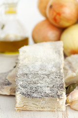 salted dry codfish with oil, garlic and onion on wooden background
