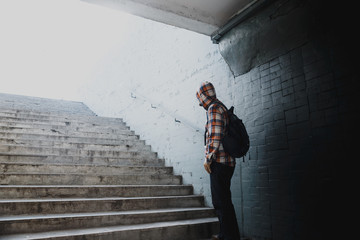 Hipster in a checkered shirt rises the stairs from the underpass