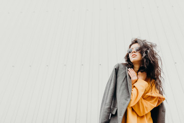 Portrait of stylish modern young curly woman in coat sunglasses. She on the street and looks happy. Truly emotions.