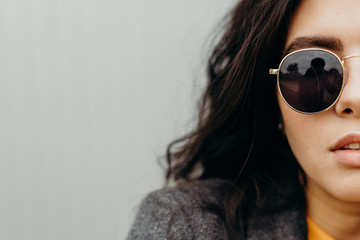 Portrait of stylish modern young curly woman in coat sunglasses
