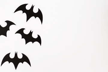 Halloween concept of paper black bats on white background. Flat lay, top view.