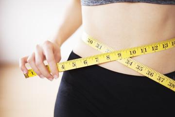 Beautiful woman in sportswear using measure in sport gym