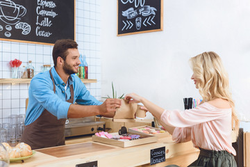 waiter giving take away food to client