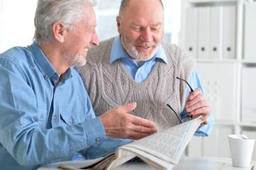 senior men reading newspaper