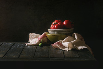 Bowl of tomatoes with pepper and linen towel on old wooden kitchen table. Dark rustic still life.