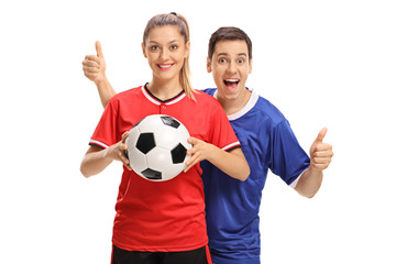 Female soccer player holding football and male soccer player holding his thumbs up