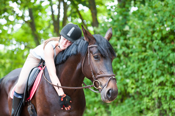 Young teenage girl-equestrian embracing her favorite frend-chestnut horse.