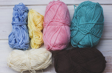 Colored cotton yarn on white wooden background